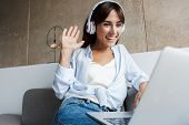 Image of a cheery smiling young woman indoors at home using laptop computer with headphones sit on s poster