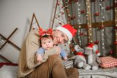 Dad And Son Hug At The Christmas Tree. A Happy Child And His Dad Are Looking Into The Frame. Dad Wit poster