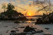 Rocky tropical coastline under warm sunset, Ko phayam island, Thailand poster