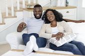 Smiling African American Couple Relaxing And Watching Tv At Home, Having Rest After Hard Week, Man S poster