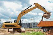 foto of boom-truck  - wheel loader excavator machine loading dumper truck at sand quarry - JPG