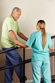 Senior man on treadmill with physiotherapist holding railing