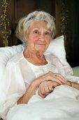 foto of nightgown  - Senior woman resting in bed sitting propped up against the pillows in her nightgown looking at the camera - JPG