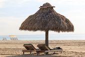 picture of tiki  - Lounge chairs under the shade of tiki huts on hot - JPG