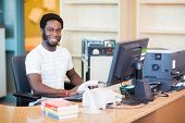 Portrait of confident male librarian working at desk in library