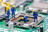 stock photo of engineering construction  - Group of construction workers repairing CPU - JPG