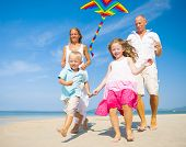 Family Running with Kite on Beach