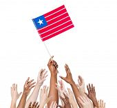 Diverse and Multiethnic Hands Holding The Flag of Liberia