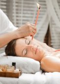 picture of ear candle  - Ear candling being carried out on an attractive caucasian woman in a spa - JPG