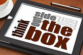 stock photo of thinking outside box  - think outside the box concept on a digital tablet with cup of tea - JPG