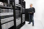 pic of racks  - It engineer or consultant standing with a laptop and monitor blade servers in data rack - JPG