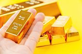 image of billion  - close up of Hand hold gold bars - JPG