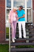 stock photo of day care center  - Care assistant helping a senior lady on steps holding her hand as they descend a set of wooden stairs outdoors on the care home