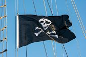 pic of skull crossbones flag  - Black skull and crossbones pirate flag against a blue sky - JPG