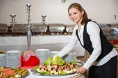 stock photo of buffet  - Catering service employee or waitress preparing a table for a buffet - JPG