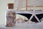 foto of life-boat  - Glass jar of sea shells in the foreground with blurred out shells and sail boat behind - JPG