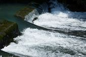 picture of dam  - Water flowing over a small rock dam - JPG
