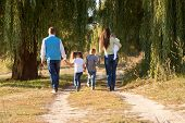 picture of extended family  - Big happy family walking on the road in the park. Father mother son daughter and baby holding hands and going together. Rear view. Family Ties concept. ** Note: Soft Focus at 100%, best at smaller sizes - JPG