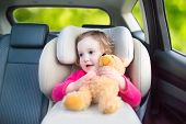 picture of car-window  - Cute curly laughing and talking toddler girl playing with a toy bear enjoying a family vacation car ride in a modern safe vehicle sitting in a baby seat with belt having fun watching out of the window - JPG