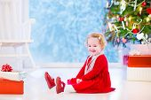 foto of girl next door  - Cute curly little girl in a red dress and white pearl necklace playing under a Christmas tree with presents sitting on the floor of a white living room with rocking chair next to a window into a snowy winter garden - JPG
