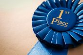 stock photo of rosettes  - Blue first place winner rosette or badge from pleated ribbon with central text to be awarded to the winner of a competition on a graduated beige background with copyspace - JPG