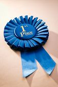foto of rosettes  - Blue first place winner rosette or badge from pleated ribbon with central text to be awarded to the winner of a competition on a graduated beige background with copyspace - JPG
