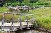stock photo of yesteryear  - Old wooden walking bridge with wagon across stream - JPG