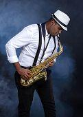 stock photo of sax  - Saxophonist black men in white shirt - JPG