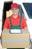picture of moving van  - Smiling young male postal delivery courier man in front of cargo van delivering boxes - JPG