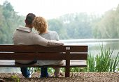 foto of sitting a bench  - Rear view of a happy couple sitting together on bench outdoors - JPG