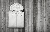 picture of hooded sweatshirt  - White hooded sweater on dark wood background - JPG