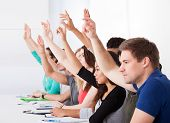 pic of students classroom  - Row of multiethnic college students raising hands in classroom - JPG