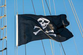 foto of skull crossbones flag  - Black skull and crossbones pirate flag against a blue sky - JPG