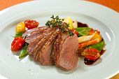 foto of roast duck  - Roasted duck in slices with thyme in port wine sauce served with cherry tomatoes sliced potatoes carrots and asparagus - JPG