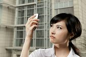 picture of angry  - Angry business woman of Asian holding cellphone and looking at it in outside of office in Taipei - JPG