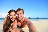 stock photo of candid  - Couple relaxing on beach taking selfie picture with camera smartphone - JPG