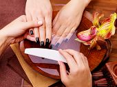 stock photo of black woman spa  - Manicurist master  makes manicure on woman - JPG