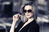 image of jacket  - Young fashion business woman in sunglasses on a city street - JPG