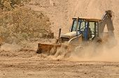 stock photo of backhoe  - Small backhoe moves dirt at a new commercial construction development project - JPG