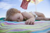 stock photo of baby diapers  - one year baby with white diaper sleeping on striped colored beach towel under parasol - JPG