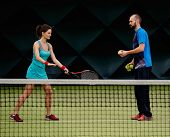 picture of  practices  - Woman player and her coach practicing on a tennis court - JPG