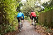 pic of bike path  - Two Mature Male Cyclists Riding Bikes Along Path - JPG