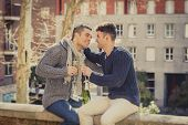 stock photo of gay couple  - young attractive Hispanic gay men couple kissing celebrating together Valentines day or anniversary champagne toast on street smiling happy in love on urban background - JPG