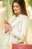 stock photo of shopping center  - Beauty woman with shopping bags in shopping mall with smartphone - JPG