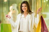 stock photo of shopping center  - Happy woman with shopping bags in shopping mall is looking at the camera - JPG