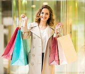 picture of shopping center  - Beauty woman with shopping bags in shopping mall is looking at the camera - JPG