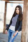 pic of jacket  - Beautiful young girl, Caucasian appearance, with dark, long, straight hair, brown eyes and beautiful dark eyebrows, wearing a striped shirt, blue jeans and black leather jacket, standing in the street, leaning against a wooden pole.