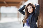 stock photo of jacket  - Beautiful young girl, Caucasian appearance, with dark, long, straight hair, brown eyes and beautiful dark eyebrows, wearing a striped shirt, blue jeans and black leather jacket, standing in the street, leaning against a wooden pole.