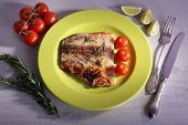 picture of pangasius  - Dish of Pangasius fillet with rosemary and cherry tomatoes in plate on color wooden table background - JPG