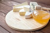 foto of brie cheese  - cheese plate with Brie Camembert Roquefort on wooden plate - JPG